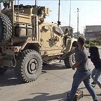 In this frame grab from video provided by Hawar News, ANHA, the Kurdish news agency, residents who are angry over the US withdrawal from Syria hurl potatoes at American military vehicles in the town of Qamishli, northern Syria on October 21, 2019. (ANHA via AP)