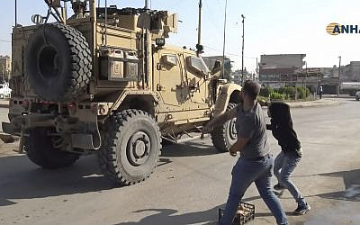 In this frame grab from video provided by Hawar News, ANHA, the Kurdish news agency, residents who are angry over the US withdrawal from Syria hurl potatoes at American military vehicles in the town of Qamishli, northern Syria, October 21, 2019. (ANHA via AP)