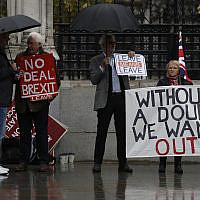 Pro-Brexit campaigners stand under umbrellas with their placards outside the Houses of Parliament in London, October 21, 2019. (Alastair Grant/AP)