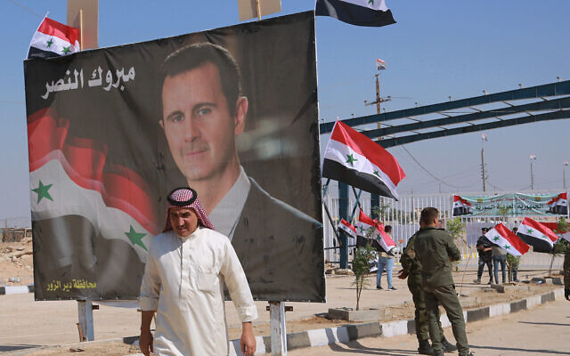 A man passes a poster of Syrian President Bashar Assad with Arabic that reads, 'Congratulations victory,' on September 30, 2019, while crossing the border into Syria at the newly opened crossing between the Iraqi town of Qaim and Syria's Boukamal, Syria. (AP Photo/Hadi Mizban, File)