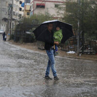 A Palestinian man holds a child under an umbrella during rainfall in Gaza City, October 26, 2019. (AP Photo/ Hatem Moussa)