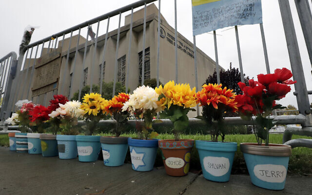 Flower pots, each with a name of one of the 11 worshipers killed on October 27, 2018, when a gunman opened fire as worship services began at the Tree of Life Synagogue, line the fence surrounding the synagogue on October 26, 2019, in the Squirrel Hill neighborhood of Pittsburgh, Pennsylvania. (AP Photo/Gene J. Puskar)