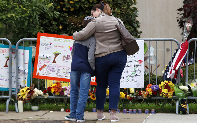 A mother hugs her son in front of a memorial at the Tree of Life synagogue in Pittsburgh on Sunday, Oct.ober27, 2019, the first anniversary of the shooting at the synagogue, that killed 11 worshipers. (AP Photo/Gene J. Puskar)