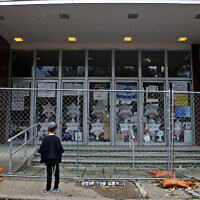 A young boy looks at the fenced off entrance to the Tree of Life synagogue in Pittsburgh on October 27, 2019, the first anniversary of the shooting at the synagogue, that killed 11 worshipers. (AP Photo/Gene J. Puskar)