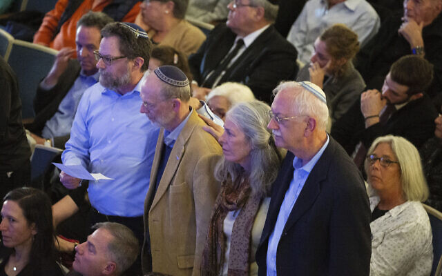 Survivors of the Tree of Life synagogue shooting stand during the one-year commemoration of the Tree of Life synagogue attack at Soldiers & Sailors Memorial Hall and Museum, Sunday, Oct. 27, 2019, in Pittsburgh. (AP Photo/Rebecca Droke)