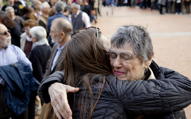 Laura Fehl, left, hugs Esther Nathanson as they arrive for the one-year commemoration of the Tree of Life synagogue attack at Soldiers & Sailors Memorial Hall and Museum, Sunday, Oct. 27, 2019, in Pittsburgh.(AP Photo/Rebecca Droke)