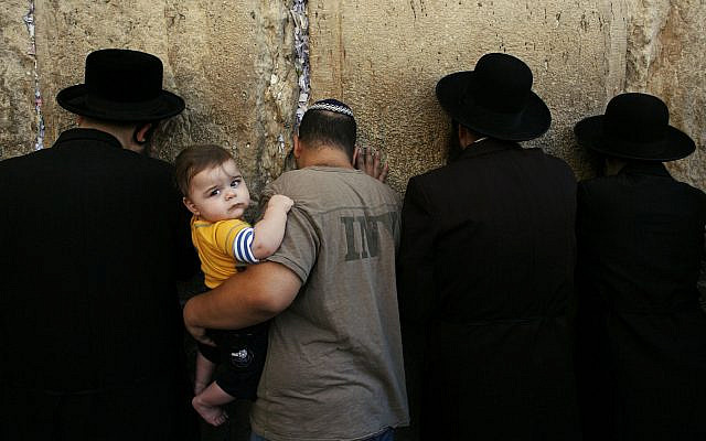 A Jewish man holds a child as he participates in morning prayers before the beginning of the Jewish holiday of Yom Kippur, at the Western Wall, Judaism's holiest site in Jerusalem's Old City, Wednesday, Oct. 8, 2008. (AP Photo/Kevin Frayer)