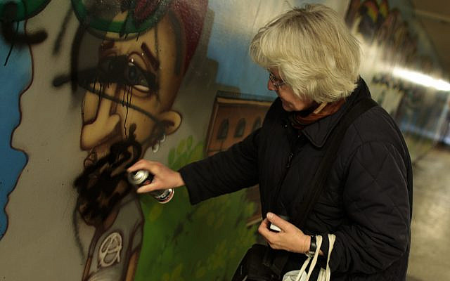 Irmela Mensah-Schramm from Berlin painting over a swastika sign on a street in Berlin's Schoeneweide district in 2011. For about the last 30 years Irmela Mensah-Schramm has walked through the streets of Berlin and other cities to paint over or remove paintings, stickers or slogans from neo-Nazis from walls, street lamps and other places. (AP Photo/Markus Schreiber)