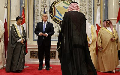 US President Donald Trump adjusts his jacket before posing for photos with leaders at the Gulf Cooperation Council meeting, at the King Abdulaziz Conference Center, May 21, 2017, in Riyadh, Saudi Arabia. (AP Photo/Evan Vucci)