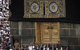 Muslim pilgrims touch the golden door of the Kaaba, the cubic building at the Grand Mosque, during the hajj pilgrimage in the Muslim holy city of Mecca, Saudi Arabia, August 13, 2019. (Amr Nabil/AP)