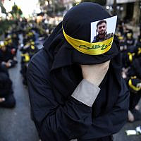 Illustrative: A Shiite supporter of the Iranian-backed Hezbollah terror group with a portrait of a dead Hezbollah fighter on his head weeps as he listens to the death story of Imam Hussein during the holy day of Ashoura, in the southern suburbs of Beirut, Lebanon, on September 10, 2019. (AP Photo/Hussein Malla)