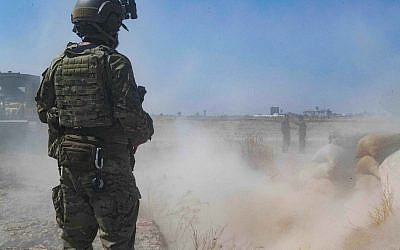 """In this Sept. 21, 2019, photo, released by the US Army, a US soldier oversees members of the Syrian Democratic Forces as they demolish a Kurdish fighters' fortification as part of the so-called """"safe zone"""" near the Turkish border. (U.S. Army/Staff Sgt. Andrew Goedl via AP)"""