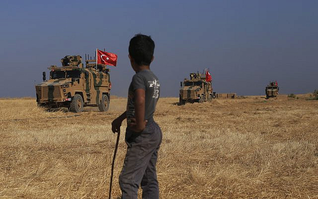 """Turkish armored vehicles patrol as they conduct a joint ground patrol with American forces in the so-called """"safe zone"""" on the Syrian side of the border with Turkey, near the town of Tal Abyad, northeastern Syria, October 4, 2019. (AP Photo/Baderkhan Ahmad)"""
