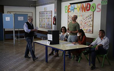 A voter casts his ballot at a polling station in Lisbon, Oct. 6, 2019. (AP Photo/Armando Franca)