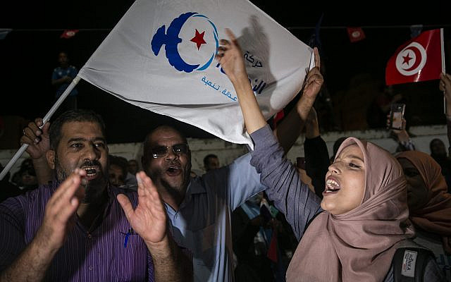 Supporters of the Islamist party Ennahda react as they follow exit polls in Tunis, Tunisia, Sunday, Oct. 6, 2019. Tunisia's moderate Islamist party appeared to be heading for victory in parliamentary elections, according to polling agencies, though the rival party of a jailed populist tycoon also claimed to come out on top of Sunday's voting. (AP Photo/Riadh Dridi)