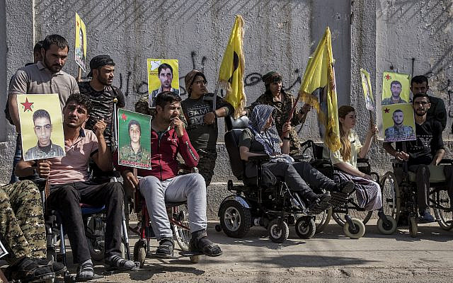 Wounded Kurdish fighters hold portraits of comrades who were killed while fighting against the Islamic State, during a demonstration against an anticipated Turkish incursion targeting Syrian Kurdish fighters, in front the United Nations building, in Qamishli, northeast Syria, Monday, Oct. 8, 2019. (AP Photo/Ahmad Baderkhan)