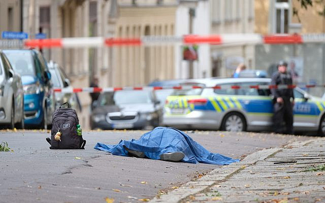 A body lies on a road in Halle, Germany, Oct. 9, 2019 after a shooting incident (Sebastian Willnow/dpa via AP)