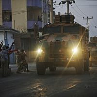 Shortly after the Turkish operation inside Syria had started, local residents cheer and applaud as a convoy of Turkish forces vehicles is driven through the town of Akcakale, Sanliurfa province, southeastern Turkey, at the border between Turkey and Syria, Oct. 9, 2019 (AP Photo/Lefteris Pitarakis)