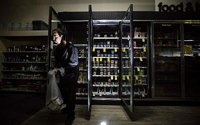 CVS Pharmacy shift supervisor James Quinn throws out ice cream from darkened freezers as downtown Sonoma, California, remains without power on Oct. 9, 2019 (AP Photo/Noah Berger)