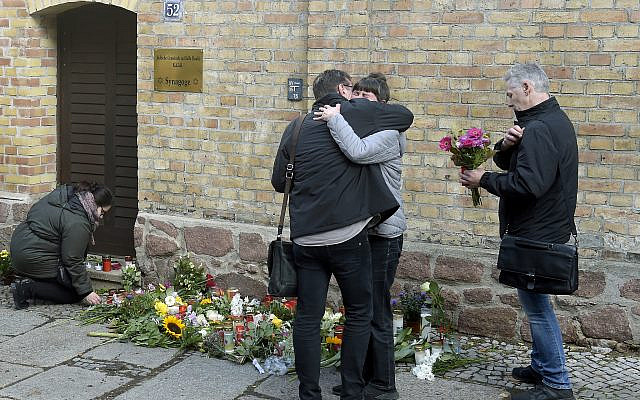 People mourn in front of a synagogue in Halle, Germany, October 10, 2019. (Jens Meyer/AP)