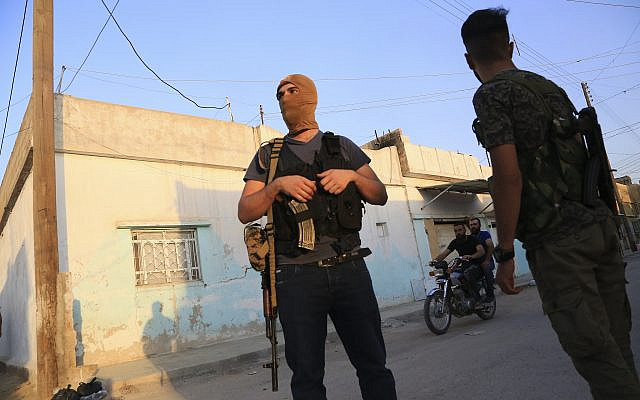 In this photo from October 10, 2019, Syrian Democratic Forces fighters stand guard in the town of Qamishli, Syria (AP Photo/Baderkhan Ahmad)