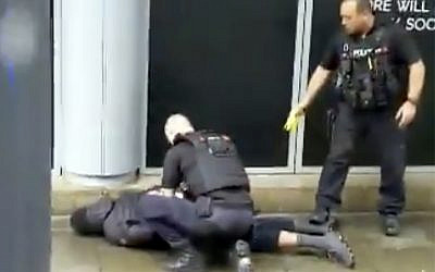 In this image taken from mobile phone footage, police arrest a man outside the Arndale Centre in Manchester, England, Friday October 11, 2019, after a stabbing incident at the shopping center that left four people injured. Greater Manchester Police say a man in his 40s has been arrested on suspicion of serious assault. He has been taken into custody. (John Greenhalgh via AP)