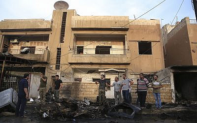 People gather after a car bomb exploded in the town of Qamishli, Syria, Friday, October 11, 2019. (AP/Baderkhan Ahmad)