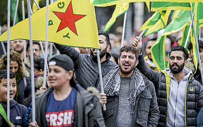 People with flags of the Kurdish YPG protest against the Turkish invasion in Kurdish territories in northern Syria in Hamburg, Germany on October 12, 2019. (Axel Heimken/dpa via AP)