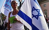 A woman with an Israeli flag protests with thousands of people on Sunday, Oct. 13, 2019 in Berlin, Germany, against rising anti-Semitism, days after a man attacked a synagogue in the eastern German city of Halle. (Paul Zinken/dpa via AP)