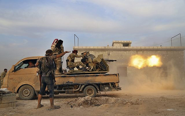 In this photo from October 14, 2019, Turkey-backed Syrian opposition fighters fire a heavy machine-gun towards Kurdish fighters, in Syria's northern region of Manbij. (AP Photo)