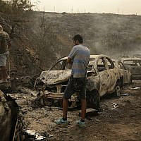 People inspect the remains of cars and shops that were burned in a wildfire overnight, in the town of Damour just over 15 kilometers south of Beirut, Lebanon, on October 15, 2019. (AP Photo/Hassan Ammar)