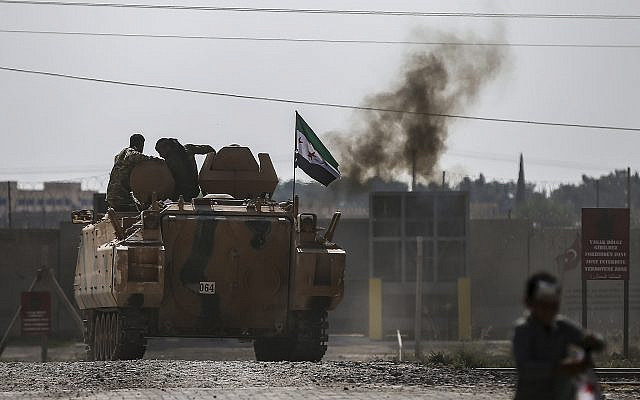 Turkish-backed Syrian opposition fighters on an armoured personnel carrier drive to cross the border into Syria, in Akcakale, Sanliurfa province, southeastern Turkey, October 18, 2019. (AP Photo/Emrah Gurel)