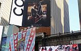 A billboard in New York City's Time Square depicts US President Donald Trump being hogtied by a woman clad in athletic wear on Oct. 18, 2019  (AP Photo/Ted Shaffrey)