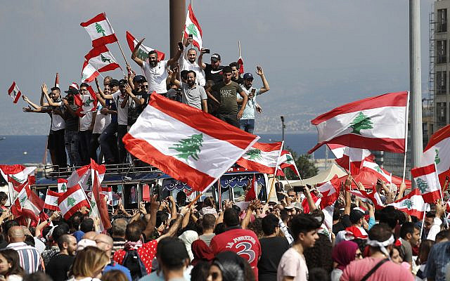 Anti-government protesters chant slogans and wave their national flags at Martyr's Square, in downtown Beirut, Lebanon, October 20, 2019. (AP Photo/Hussein Malla)