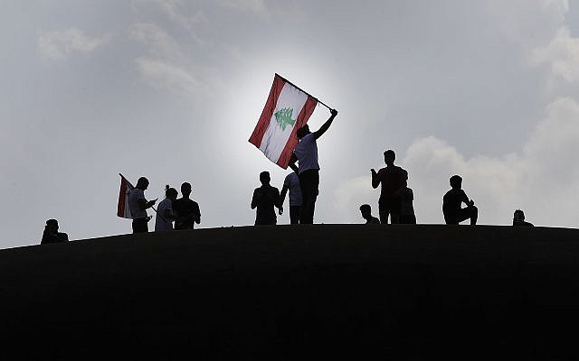 """Anti-government protesters wave a Lebanese flag, as they stand on the Dome City Center known as """"The Egg,"""" an unfinished cinema leftover from the civil war, as they watch other protesters, in downtown Beirut, Lebanon, October 20, 2019. (AP Photo/Hussein Malla)"""