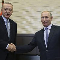 Russian President Vladimir Putin, right, and Turkish President Recep Tayyip Erdogan shake hands before their meeting in the Bocharov Ruchei residence in the Black Sea resort of Sochi, Russia, October 22, 2019. (Presidential Press Service via AP, Pool )