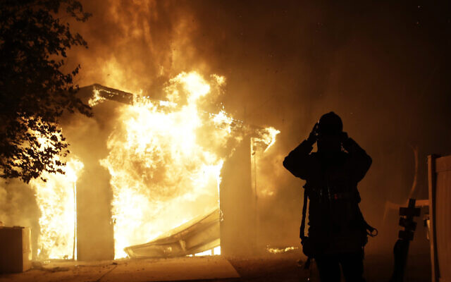 A firefighter prepares to fight a wildfire as it overtakes a home October 24, 2019, in Santa Clarita, California (AP Photo/Marcio Jose Sanchez)