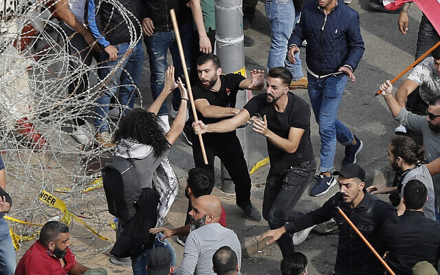 Anti-government protesters, left, and Hezbollah supporters, right, clash during a protest near the government palace, in downtown Beirut, Lebanon, October 25, 2019. (AP Photo/Hussein Malla)