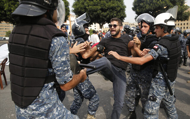 Police remove an anti-government protester blocking a main highway with his body in Beirut, Lebanon, October 26, 2019 (AP Photo/Hussein Malla)