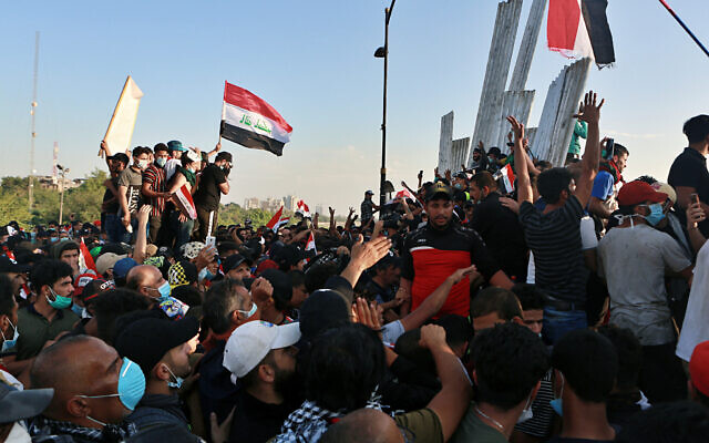 Anti-government protesters remove barriers on a bridge leading to the Green Zone during a demonstration in Baghdad, Iraq, October 26, 2019. (AP/Khalid Mohammed)