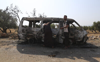 People look at a destroyed van near the village of Barisha, in Idlib province, Syria, October 27, 2019, after an operation by the US military which killed IS chief Abu Bakr al-Baghdadi. (AP/Ghaith Alsayed)