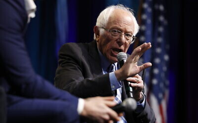 Democratic presidential candidate Bernie Sanders speaks at the J Street National Conference, with the 'Pod Save the World' hosts Tommy Vietor, left, and Ben Rhodes, October 28, 2019, in Washington. (AP Photo/Jacquelyn Martin)