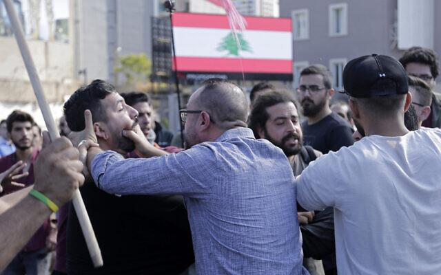 Hezbollah supporters, foreground, fight with an anti-government protester during clashes erupted between them during ongoing protests against the Lebanese government in Beirut, Lebanon, October 29, 2019 (AP Photo/Hassan Ammar)