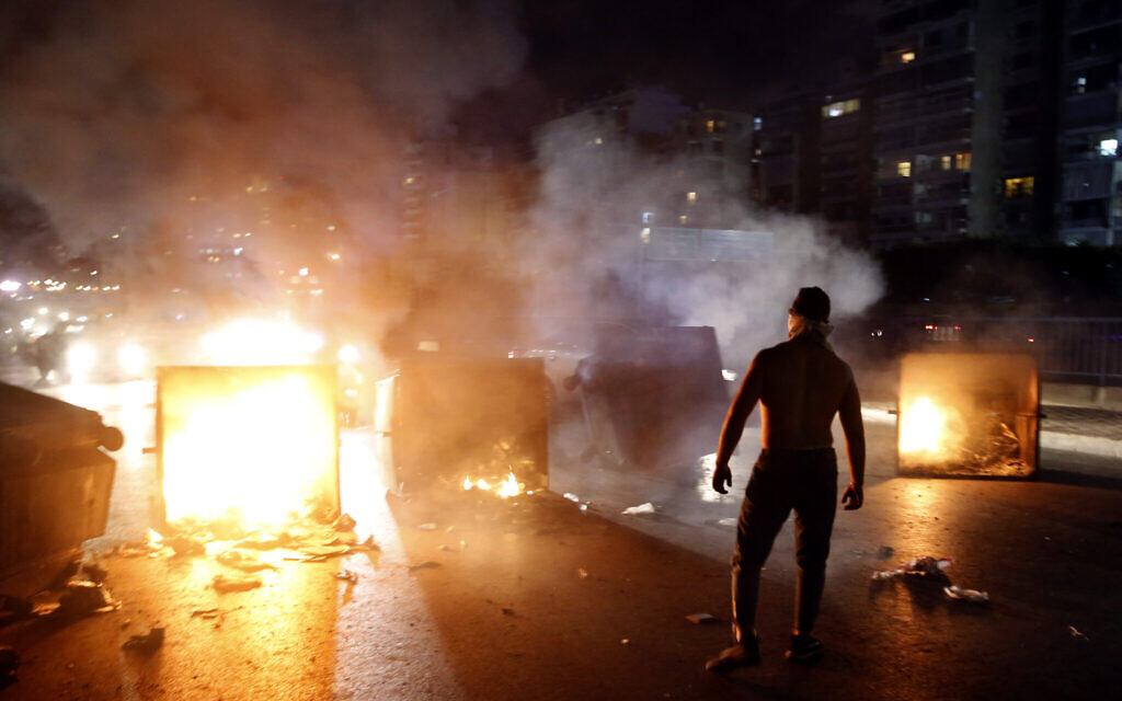 A supporter of Lebanese Prime Minister Saad Hariri burns garbage containers to block  a main road, in Beirut, Lebanon, October 29, 2019. (AP Photo/Bilal Hussein)