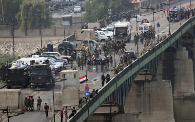 Security forces fire tear gas and close the bridge leading to the Green Zone during a demonstration in Baghdad, Iraq, October 30, 2019.  (AP Photo/Hadi Mizban)
