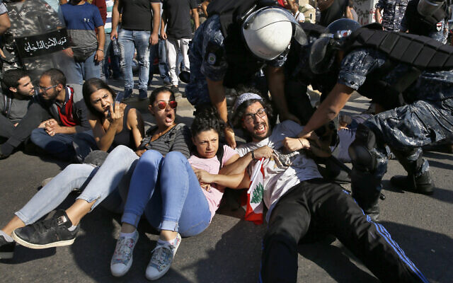 Anti-government protesters lie on a road, as they scream and hold each others while riot police try to remove them and open the road, in Beirut, Lebanon, Oct. 31, 2019 (AP Photo/Bilal Hussein)