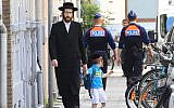 Illustrative: An Orthodox Jew and a boy pass two police officers in Antwerp, Belgium, on May 25, 2014. (AP Photo/Yves Logghe)