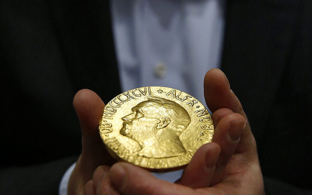 Bidder Ole Bjorn Fausa, of Norway, holds the 1936 Nobel Peace Prize medal in Baltimore, March 27, 2014, the second Nobel Peace Prize ever to come to auction. (AP Photo/Patrick Semansky)