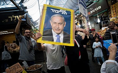 A Likud party supporter holds a campaign poster featuring Prime Minister Benjamin Netanyahu at Jerusalem's Mahane Yehuda market on April 7, 2019. (Yonatan Sindel/Flash90)