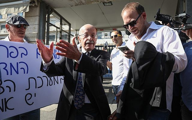 Prime Minister Benjamin Netanyahu's lawyer Ram Caspi (2nd-L) outside the Justice Ministry headquarters on October 2, 2019, ahead of Netanyahu's pre-indictment hearing. (Noam Rivkin Fenton/Flash90)